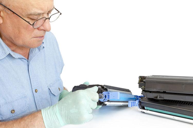 Man repairing computer printer against white background