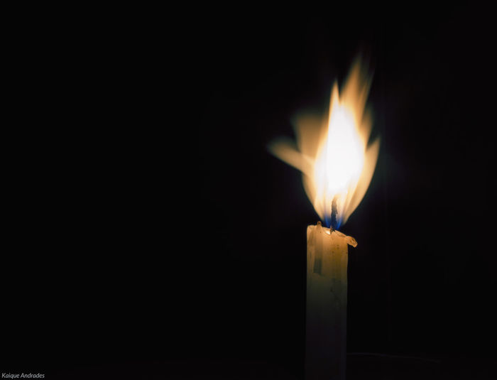 Close-up of candle burning against black background
