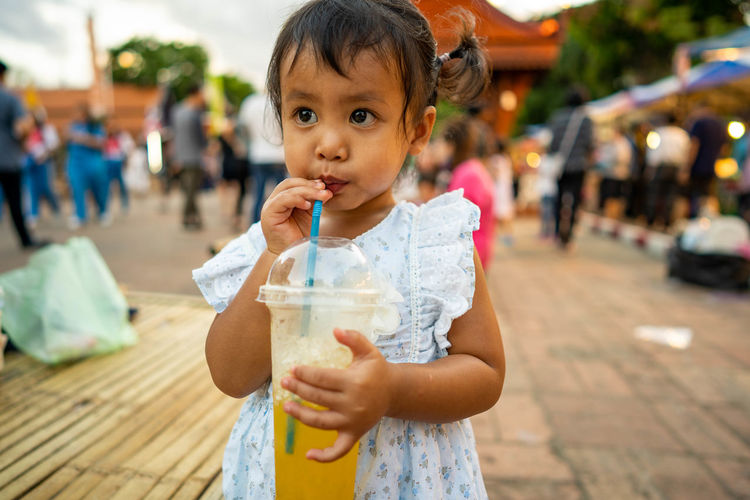 Cute girl drinking while standing outdoors