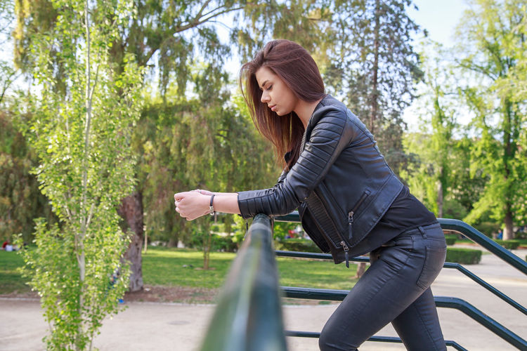 Side View Of Young Woman With Long Hair Standing By Railing Against Trees In Park