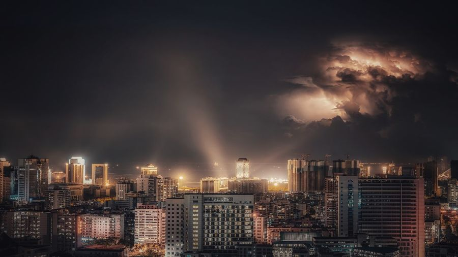 Panoramic view of buildings in city against sky at night