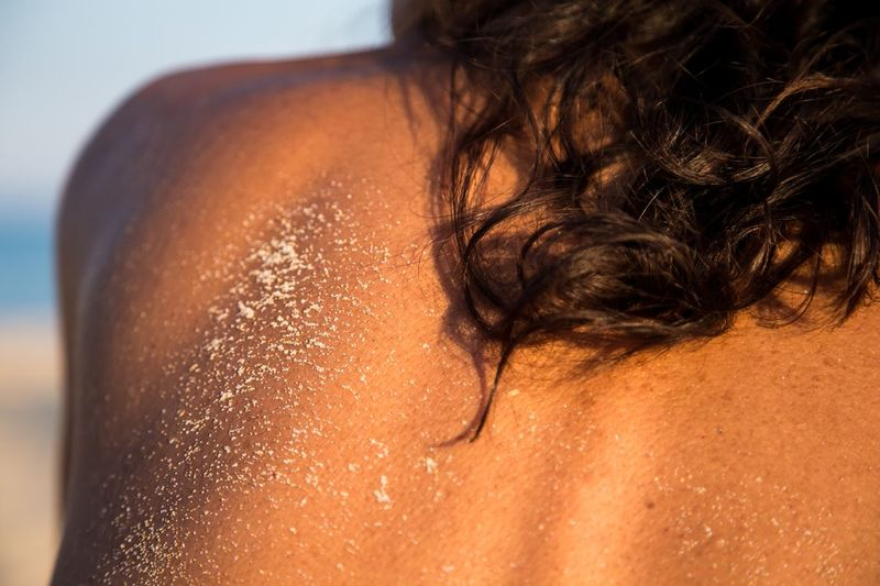 Close-up of sand on woman back