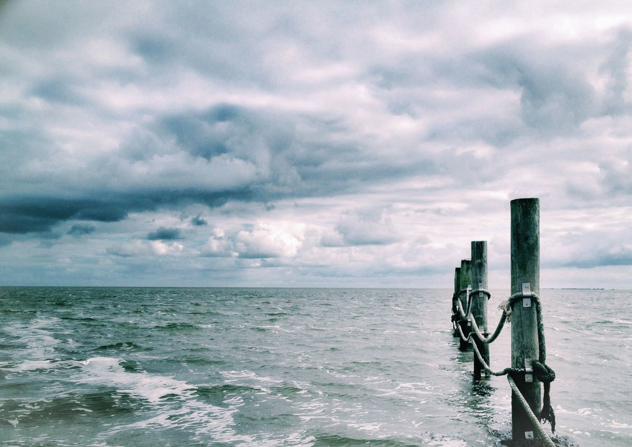 Cloudy sky with wooden poles in water