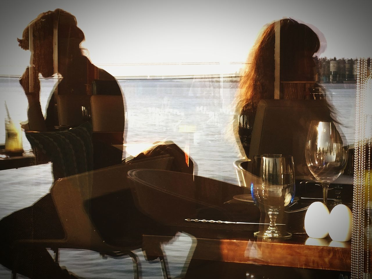 indoors, table, real people, women, one person, food and drink, water, lifestyles, sea, wine, sitting, wineglass, men, day, sky, people
