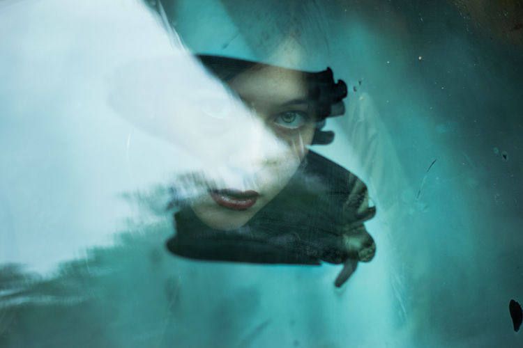 Portrait of woman seen through wet window