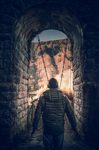 man at the entrance of an ancient bridge Arch Real People Architecture Men Clothing Mistery Entrance Adventure Dark