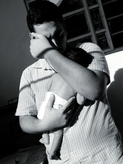 Man carrying newborn baby while standing against window