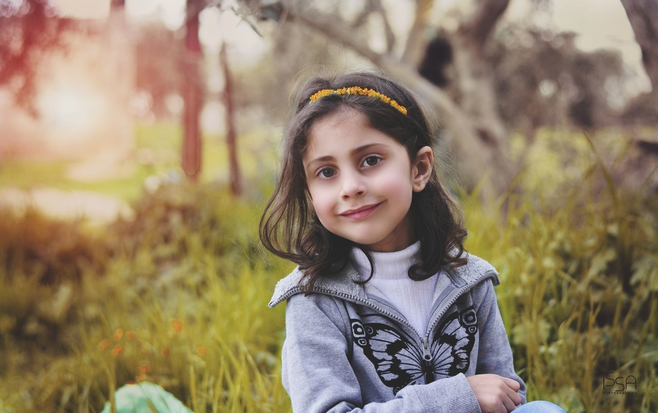 childhood, looking at camera, focus on foreground, real people, portrait, one person, girls, outdoors, elementary age, smiling, day, standing, grass, nature, close-up