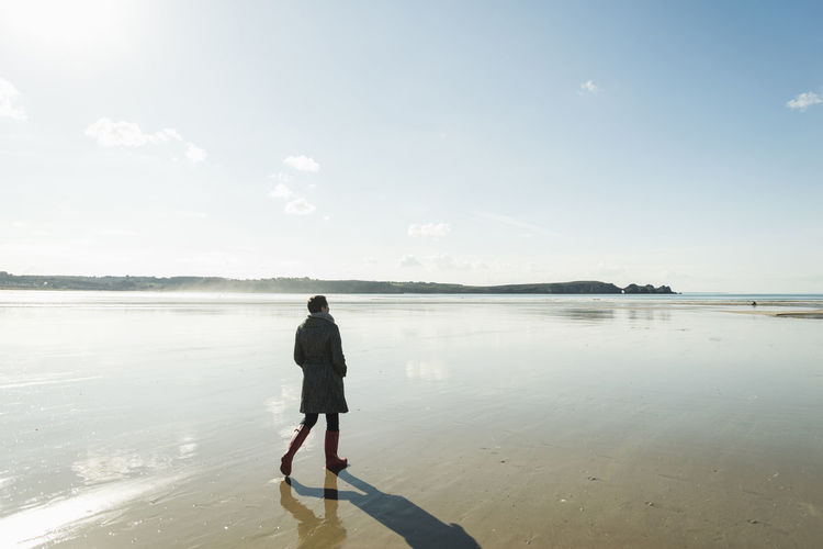 Rear view of man standing at beach against sky