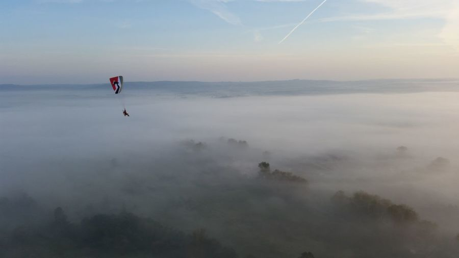 Distant View Of Person Paragliding Over Landscape During Foggy Weather