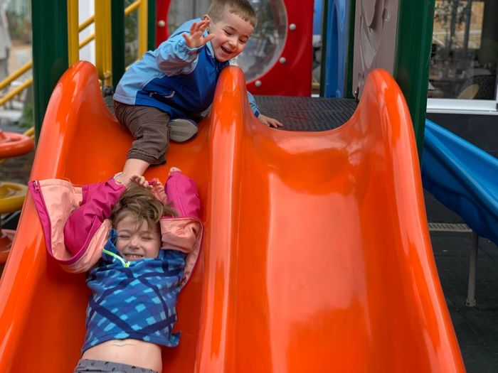Happy siblings playing on slide at playground