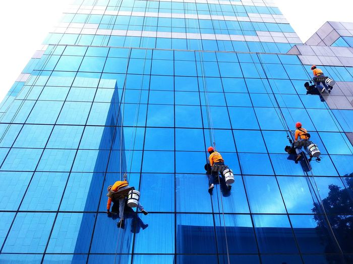 Low angle view of men working on building. cleaning worker
