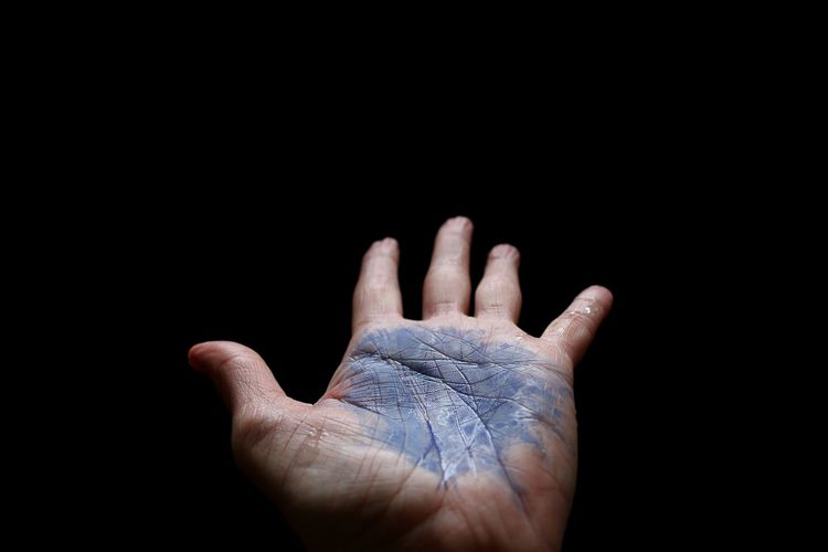 Cropped Image Of Dirty Hand Against Black Background