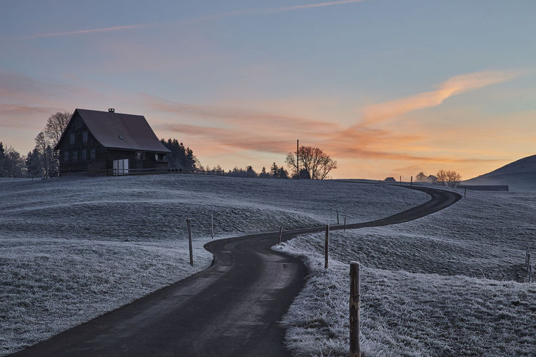 Road Architecture Beauty In Nature Building Building Exterior Built Structure Cloud - Sky Cold Temperature Covering Environment Field House Nature No People Outdoors Road Sky Skyfire Snow Sunset Tree Winter