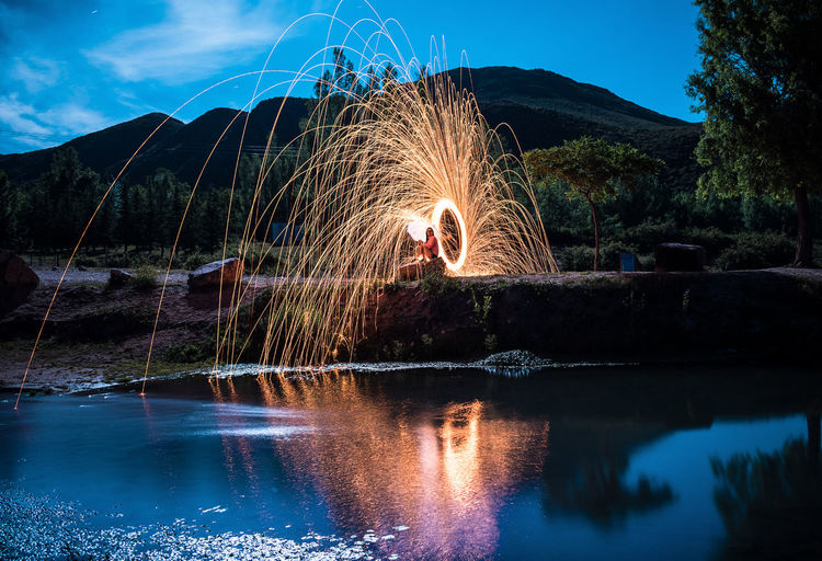 View of firework display over lake against sky