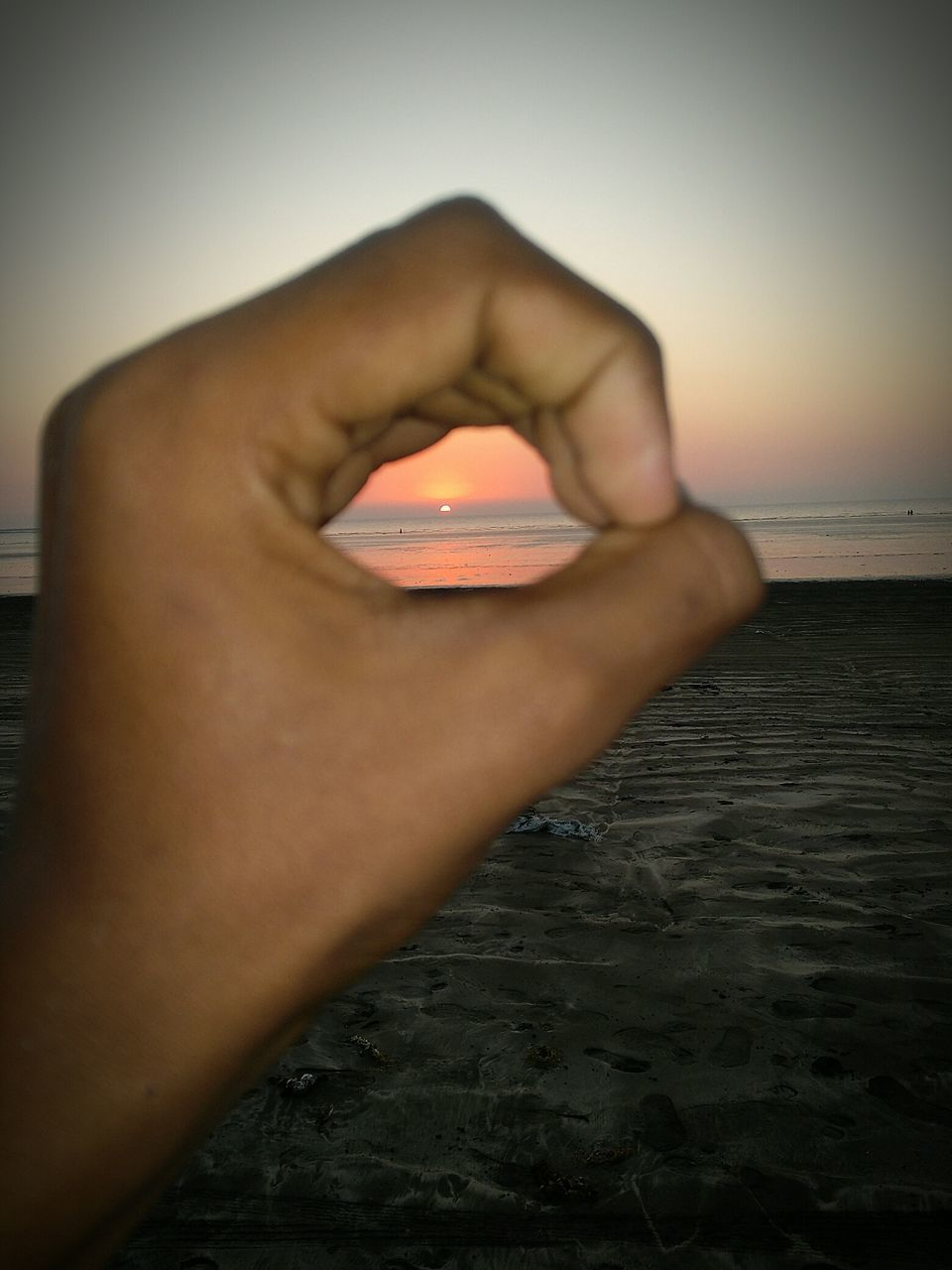human hand, human body part, human finger, one person, sea, sunset, holding, optical illusion, close-up, beach, real people, outdoors, nature, sky, water, beauty in nature, day, adult, people