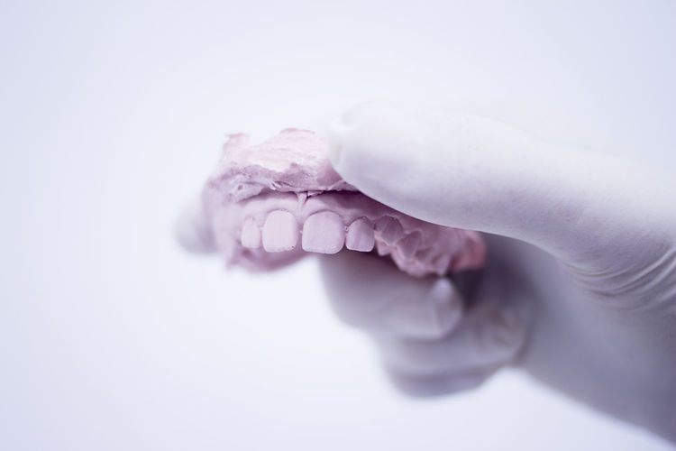 Close-up of hand holding dentures against white background