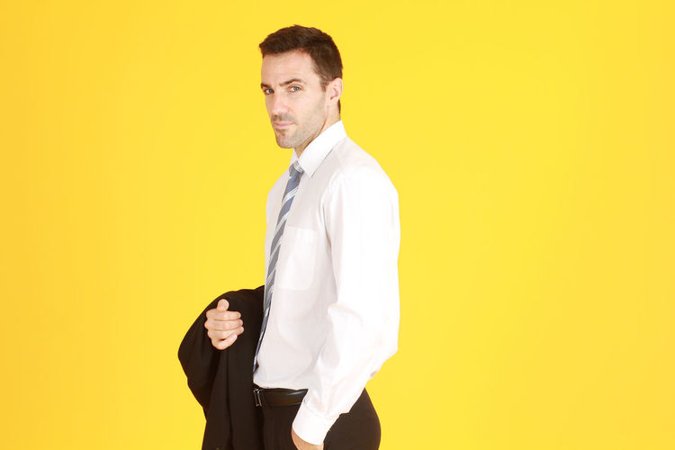 Portrait of young man standing against yellow background