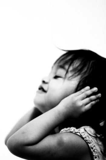 Close-up of girl with hands covering ears on white background