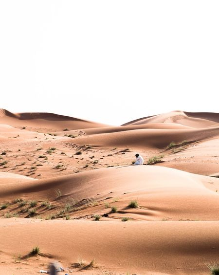 Man Sitting On Desert Against Clear Sky