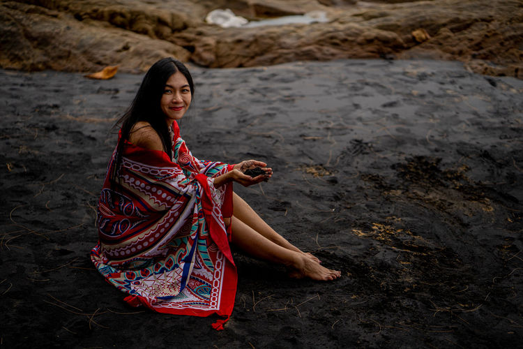 Portrait of smiling young woman sitting on land