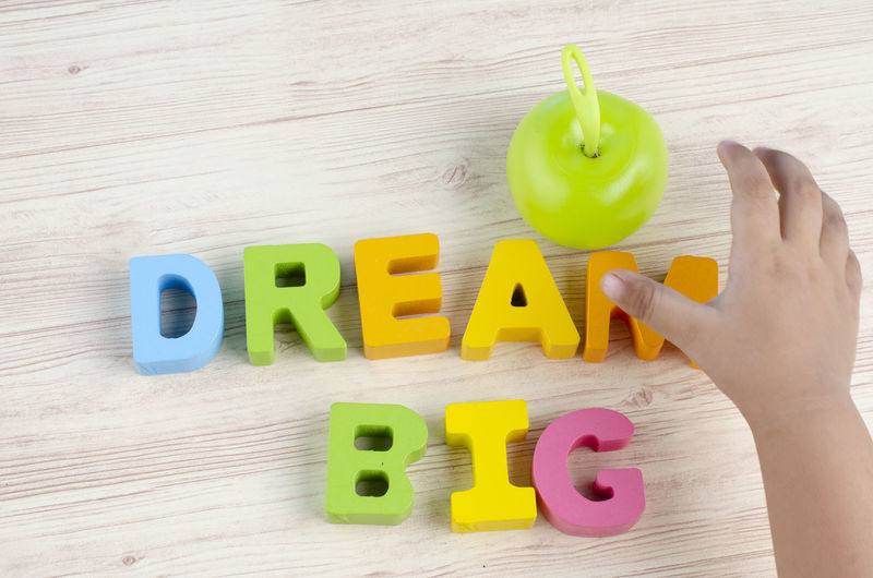 DREAM BIG word on wooden desk over blue background Text Western Script Hand One Person Human Hand Capital Letter Indoors  Real People Alphabet Human Body Part Letter Communication Table Multi Colored Holding Wood - Material Body Part Personal Perspective Lifestyles Finger