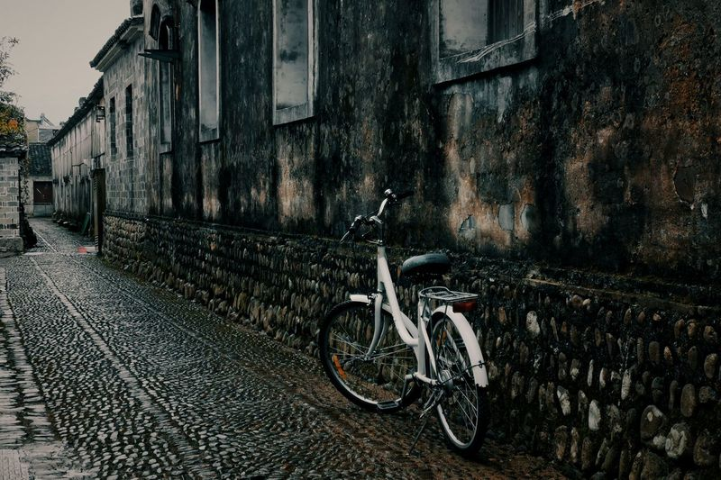 Bicycle parked on street amidst buildings