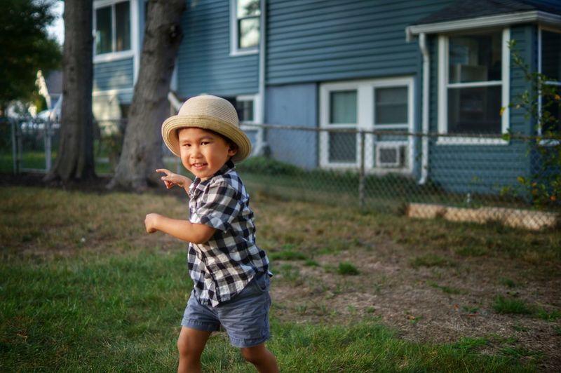 Portrait of smiling boy walking on field