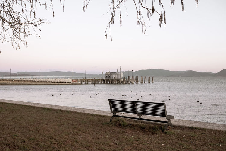 Empty bench on beach against clear sky