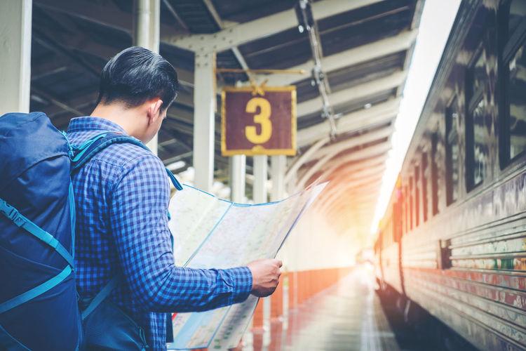 Man reading map while standing at railroad station platform