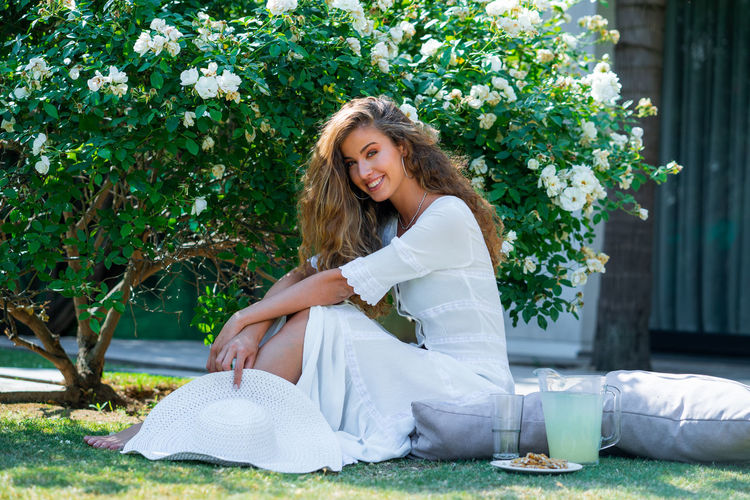 Portrait of smiling young woman against white plants