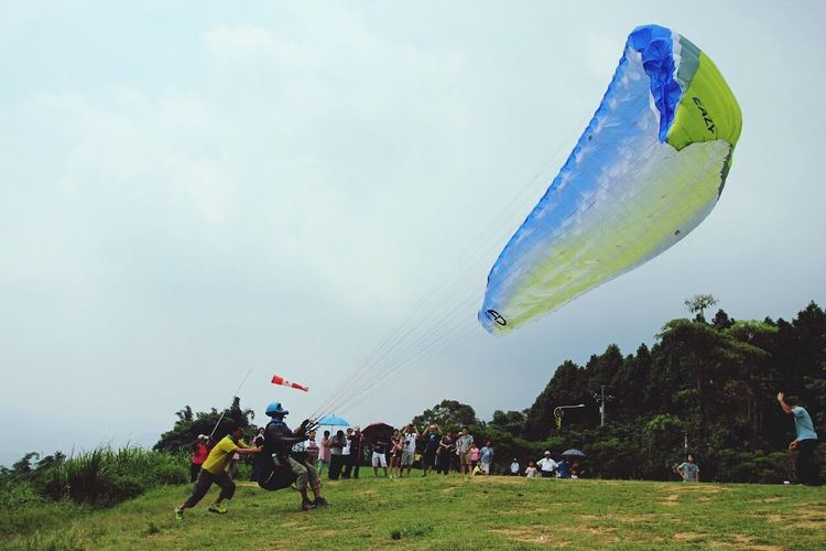 Man helping paraglider to take off against sky