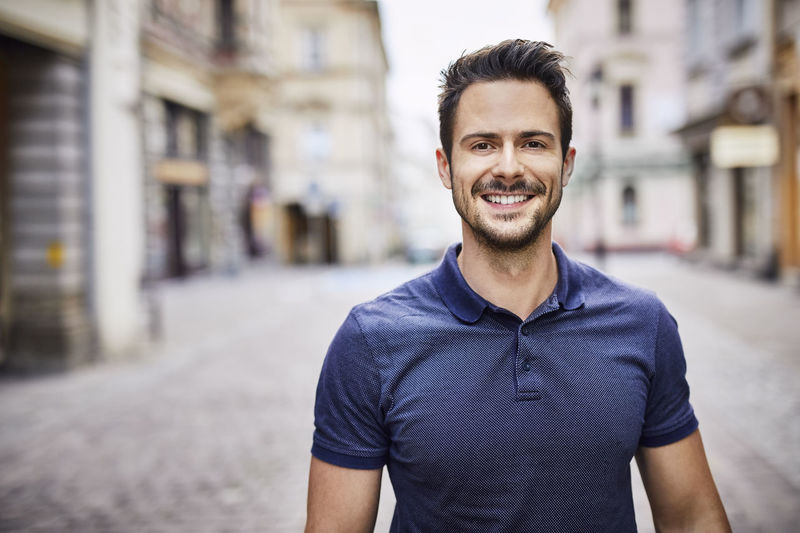 Portrait of smiling young man standing against city