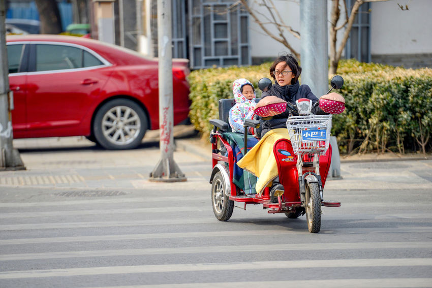 BEIJING, CHINA People are driving through the streets with bicycles, scooters and cars. ASIA Asian  Beijing Beijing, China City Exotica Lifestyle Rickshaw Run Road Tourists Transportation Bicycle Capital Cities  China Destination Ecology Hutong Old Parked Ride Street Tourism Trafic Urban Vintage
