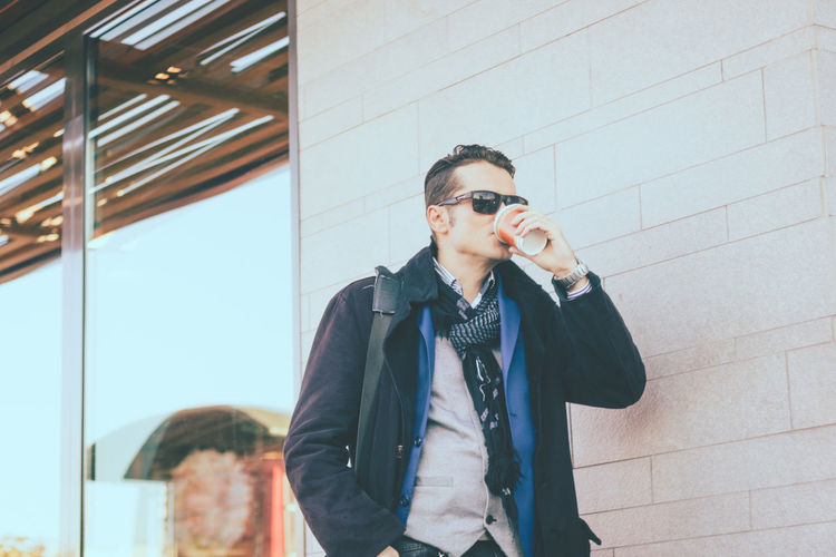 Fashionable man drinking coffee against wall outdoors