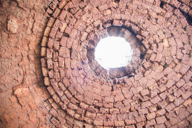 Low angle view of stone wall with hole