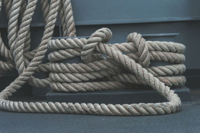 Close-up of ropes tied to metal on boat