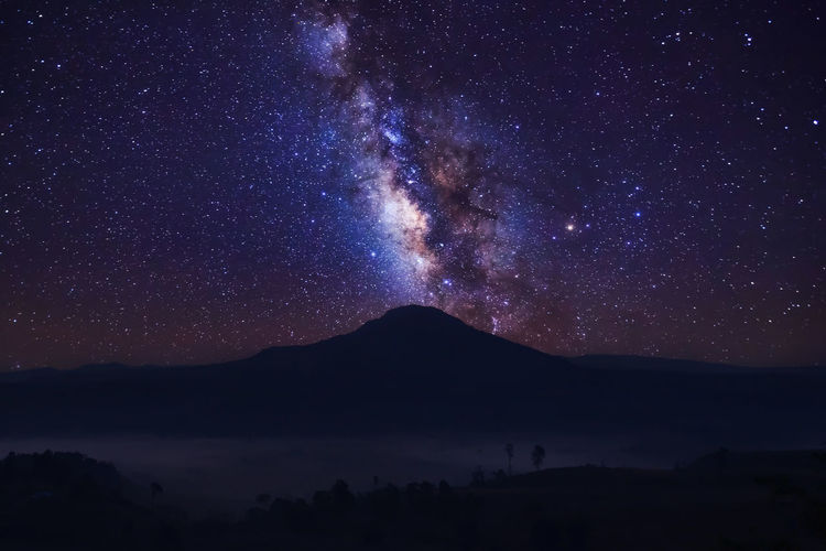Silhouette mountain against star field at night