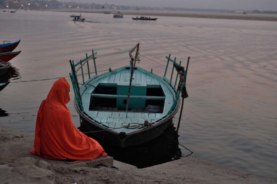 man sitting at ghats varanasi Boat Contemplation Evening Scene India Man Sitting Mediation Silence Tranquil Scene Tranquility Varanasi Varanasi Ghats Water
