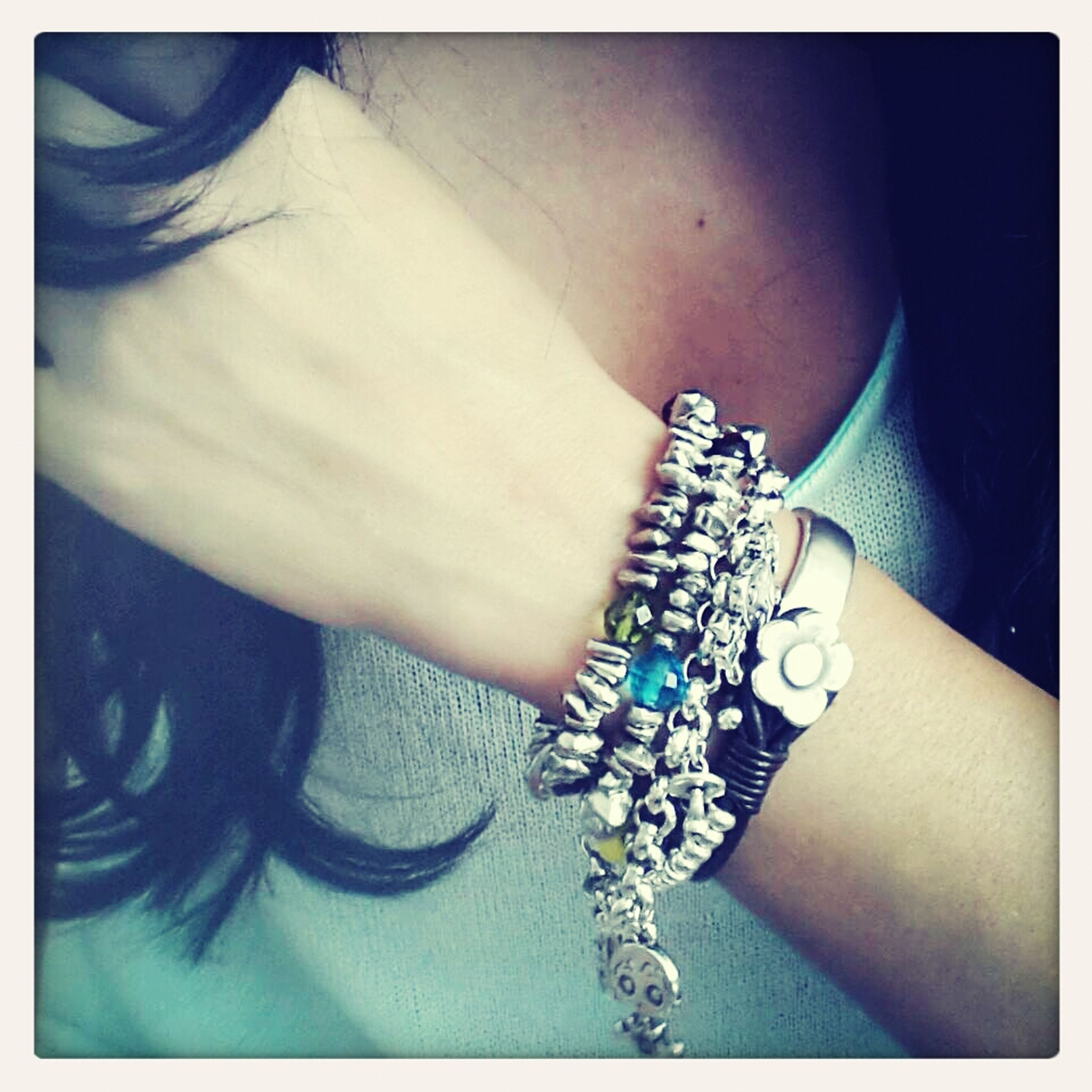 indoors, person, lifestyles, part of, leisure activity, fashion, close-up, holding, transfer print, high angle view, auto post production filter, jewelry, human finger, unrecognizable person, bracelet, cropped