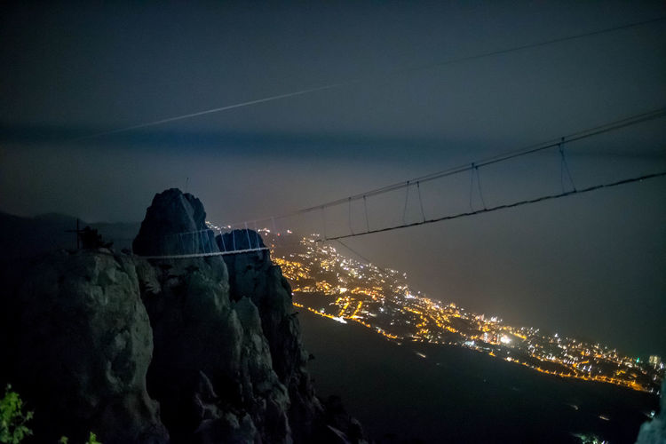 Illuminated Night Sky Nature Architecture No People Built Structure Water Connection Cable Mountain Outdoors Building Exterior Tranquil Scene Dusk Rock Beauty In Nature Tranquility Cloud - Sky