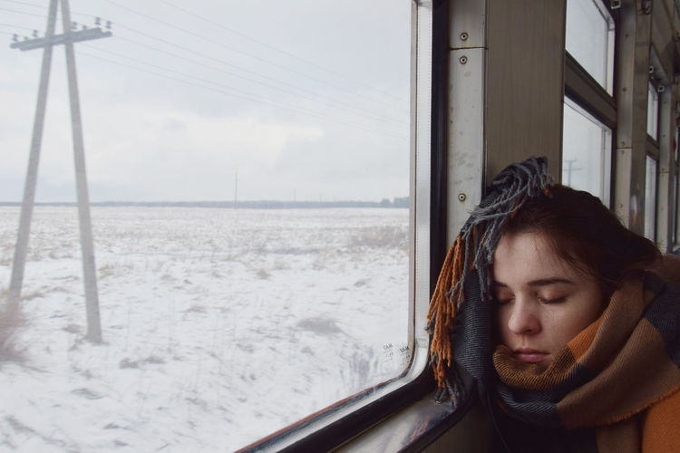 Woman Sleeping By Window In Train During Winter