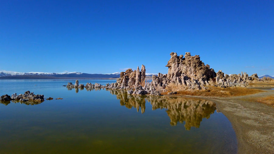 Rock formation in water against clear blue sky