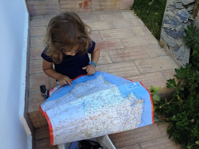High angle view of girl with map sitting on steps