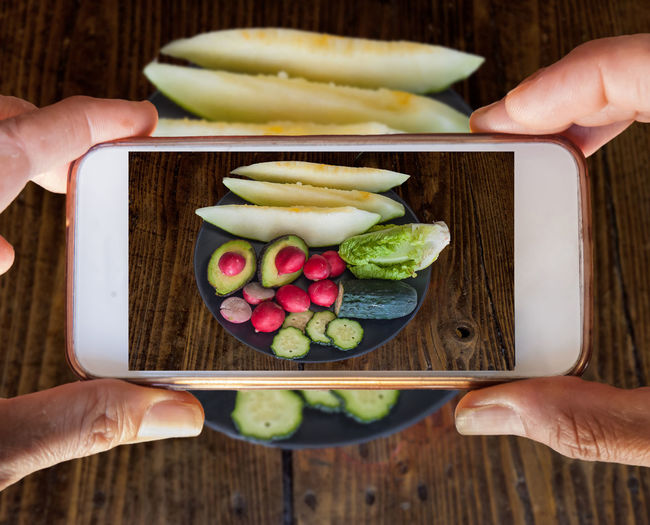Tow hands holding a mobile phone taking a photography of vegetables and fruits Adult Body Part Finger Food Food And Drink Freshness Fruit Hand Healthy Eating Holding Human Body Part Human Hand Human Limb Leisure Activity Lifestyles Movile Camera Movilephotography One Person Real People Table Unrecognizable Person Vegetable Wellbeing Women