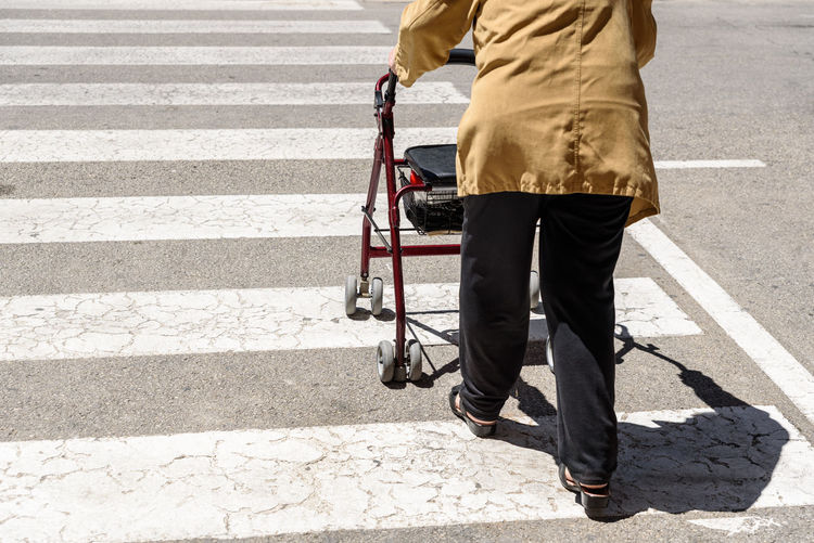 Low section of man walking on road