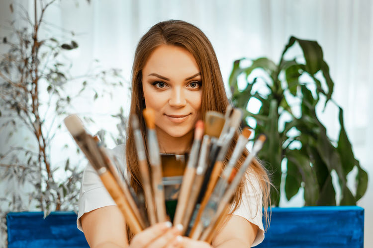 Portrait of smiling young woman holding paintbrush