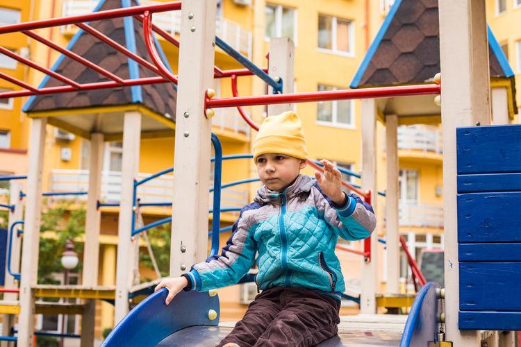 Full length of happy girl standing on slide in playground