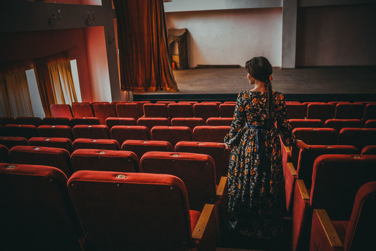 Rear view of woman standing by seats at theater