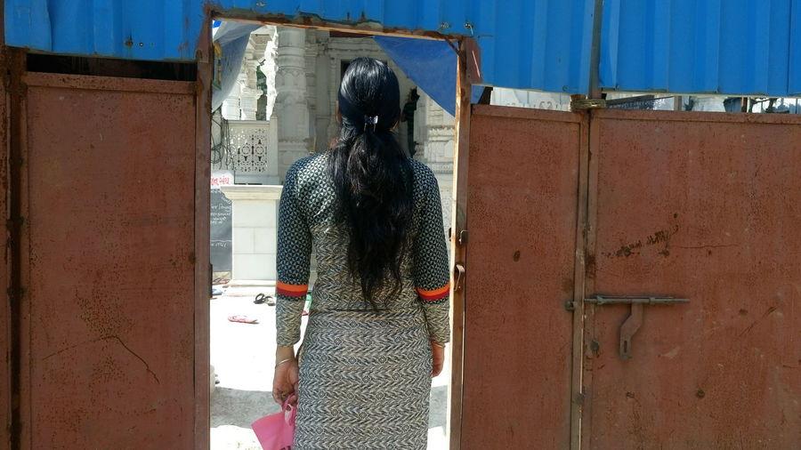 Rear View Of Woman Entering Gate